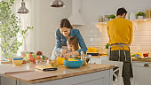 In Kitchen: Mother and Cute Little Daughter Cooking Together Healthy Dinner. Mom Teaches Little Girl Healthy Habits and how to Cut Vegetables for Salad. Cute Child Helping Her Beautiful Caring Parents