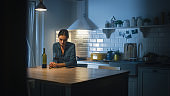 Portrait of Beautiful Lonely Young Woman Drinking from a Wine Glass in the Dark Kitchen. Depressed and Sad Adult Girl with Alcohol Problem Drinks Alone, Bad Relationships, Work Stress, Other Problems