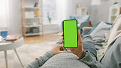 Man at Home Lying on a Couch using Smartphone with Green Mock-up Screen, Doing Swiping, Scrolling Gestures. Guy Using Mobile Phone, Internet Social Networks Browsing. Point of View Shot.
