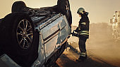 On the Car Crash Traffic Accident: Paramedics and Firefighters Rescue Injured Trapped Victims. Medics give First Aid to Female on Stretchers. Firemen Use Hydraulic Cutters Spreader to Open Vehicle