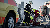 On the Car Crash Traffic Accident Scene: Paramedics and Firefighters Rescue Injured Victims Trapped in the Vehicle. Medics Use Stretchers, Perform First Aid.