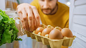Shot from Inside Kitchen Fridge: Handsome Man Opens Fridge Door, Looks inside Takes Few Eggs from Eggs Box. Man Preparing Healthy Meal. Point of View POV Shot from Refrigerator full of Healthy Food