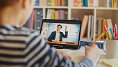 Smart Little Boy Uses Digital Tablet for Video Call with His Teacher. Screen Shows Online Lecture with Teacher Explaining Subject from a Classroom. E-Education Distance Learning, Homeschooling