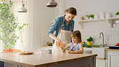 Breakfast in the Kitchen: Young Beautiful Mother Pours Cereal into Bowl, Adorable Little Daughter Starts Eating with Pleasure. Caring Mother Prepares Cereal Breakfast for Her Cute Little Girl