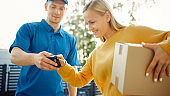 Beautiful Young Woman Meets Delivery Man who Gives Her Cardboard Box Package, She Signs Electronic Signature POD Device. Courier Delivering Parcel in the Suburban Neighborhood.