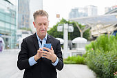 Mature businessman using phone in the city streets outdoors