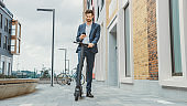 Young Businessman is Checking his Smartphone While RIde to Work on an Electric Scooter. Modern Entrepreneur Uses Contemporary Ecological Transport to Go on an Office Meeting.