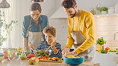 In Kitchen: Family of Three Cooking Together Healthy Dinner. Dad and Mom Teach Little Son Healthy Habits and how to Mix Vegetables in Salad Bowl. Cute Child Helping His Beautiful Caring Parents