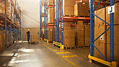Worker Moves Cardboard Boxes using Manual Pallet Truck, Walking between Rows of Shelves with Goods in Retail Warehouse. People Work in Product Distribution Logistics Center. Side View