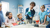 Elementary School Science / Chemistry Classroom: Teacher Shows Chemical Reaction Experiment to Group of Children. Mixing Chemicals in Beaker to get Reaction. Children Use Digital Tablet Computers