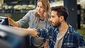 University Library: Bright Caucasian Girl and Talented Boy Study for Exams, Work on Assignment, Use Computer, Point at Screen,Talk, Look for Solution, Explain Subject. College Students Work Together