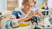 Smart Schoolboy Builds / Constructs Small Robot and Uses Laptop to Program Software for Robotics Engineering Class. School Science Classroom with Gifted Brilliant Children Working with Technology