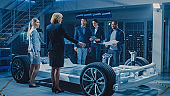International Team of Automobile Design Engineers Introducing Futuristic Autonomous Electric Car Platform Chassis to Group of Investors and Businesspeople. Vehicle Frame with Wheels, Engine, Battery