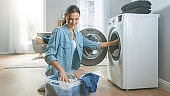 Beautiful and Happy Brunette Young Woman Comes Towards the Washing Machine in Homely Jeans Clothes. She Loads the Washer with Dirty Laundry. Bright and Spacious Living Room with Modern Interior.