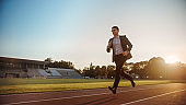 Young Serious Businessman in a Suit Running in an Outdoors Stadium. He Wears Glasses and is Holding a Mobile Phone. Office Worker Chasing Goals. Management Satire.