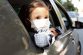 Little girl wearing masks while riding to school in the car