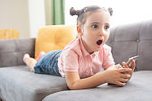 Little girl with mobile phone on couch