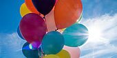 Colorful balloons with cloudy sky and sun in background