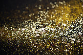 Beautiful Christmas light background. Abstract glitter bokeh and scattered sparkles in gold color, on black