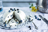 Homemade tasty cold dessert of yogurt , blueberries and gelatin, decorated with raw berries in white tablecloth  background