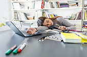 Female student who fell asleep on the desk in the library with a pile of books