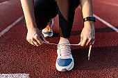 Tying shoelaces before a run on stadium. Low angle image