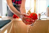 Human hands washing fresh potatoes