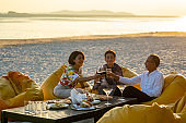 Group of Happy two generation Asian family enjoy dinner party together on the beach at sunset. Smiling senior parents with adult daughter relax and having fun together on summer holiday vacation
