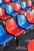 Multi-colored seats in the stadium got wet in the rain. Dirty stools on the street.