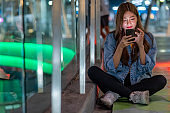 Happy young beautiful Asian woman using smartphone with internet for social media or online shopping in the city at night with illuminated city night lights background. Pretty girl enjoy and having fun with city nightlife.