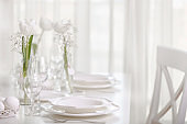 Happy Easter! Decor and table setting of the Easter table with white tulips and dishes of white color.