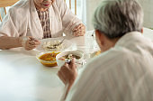 Asian senior couple eating Thai food together at home with happiness