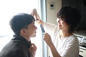 Women cutting men's hair