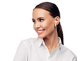 Headshot portrait of business girl wearing white shirt, wireless earphones, looking away with friendly confident smile, isolated on white background