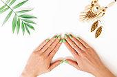 Female hands with beautiful stylish green manicure.