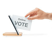 Male hand putting a ballot into a mobile phone, concept of online voting.