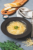 Russian homemade chicken noodle soup with dill in a dark gray plate