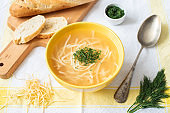Russian homemade chicken noodle soup with dill in a yellow bowl