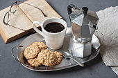 Homemade oatmeal walnut cookies, cup of coffee and coffee maker on a metal tray