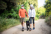 Active Seniors Hiking on a Trail with their Dog
