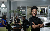 Young African businesswoman standing confidently in a modern office