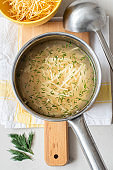 Russian homemade chicken noodle soup with dill in a metal saucepan