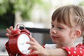 Girl holds alarm clock, carefully looks details
