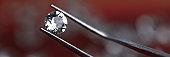 Close up metal tongs holding transparent diamond