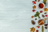 Autumn composition on a grey wooden background of dry leaves, rosehip tea, jars of honey, red berries. Top view, horizontal, with space