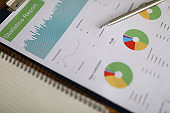 Business chart with silver pen lie on office table closeup