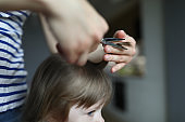 Woman doing haircut to child in an apartment