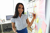Beautiful smiling brunette caucasian woman writing something on whiteboard