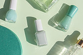 flat lay of mint color nail polishes, beauty serum, parfume and gift box on a green background