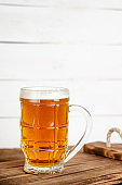 Full glass of blonde beer on white wooden backgroud. Vertical, copy space